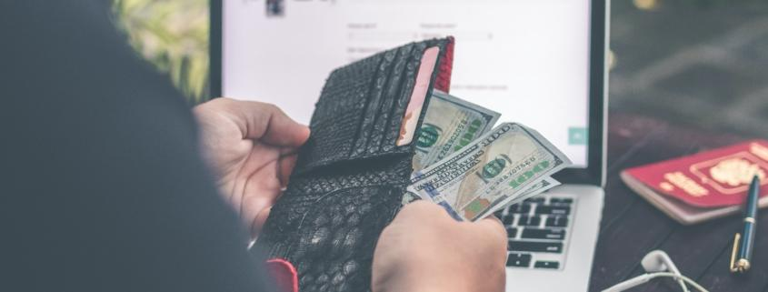 Person holding 100 U.S. dollar bill in front of laptop